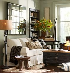 wall color, chic mirror, comfy couch, plant decor, dark wood bookshelf/ tables, white window frames