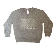 Our new WE ARE WAVES OF ONE SEA pencil print in white on a grey American Apparel tri-blend raglan pullover. A lightweight, crewneck pullover for kids in a soft Tri-Blend construction. Printed with eco