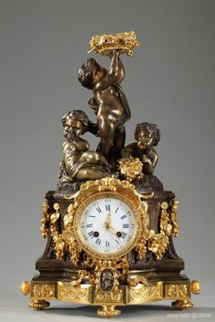 A gilt and patinated bronze mantel clock in Louis XVI style surmounted by three putti on a rock above a fluted column containing the movement. The first one plays a horn, the second holds a basket of fruits and the third one raises over his head a basket filled with flowers and fruits. White enameled dial, with Roman numerals for hours and Arabic for minutes, against a coloumn-shaped case richly decorated with garlands and medallion.