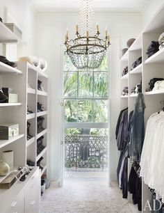Beautiful Closet Featured in Architectural Digest. Love the Window & Chandalier & the Organization from the white shelving!
