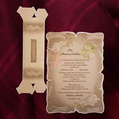 Invitatia infatiseaza o coala de papirus in carton maro ornata cu un design floral in relief si cu auriu. In partea dreapta jos si stanga sus sunt imprimati trandafiri, in relief, cu frunzele aurii iar in partea dreapta sus sunt imprimate doua inimioare aurii, in care pot fi  inscriptionate initialele mirilor.  Cutia hexagonala are aceleasi elemente si este inclusa in pret.  #invitatie de #nunta #mirese #miri #invitatii #elegante #originale
