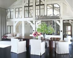 Meg Ryan's Dining Room.  Love the windows, beams, massive vintage sign and hits of pink and green against white and dark wood tones.