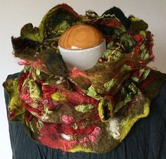 This wonderfully luxurious shibori and nuno felted cowl/ collar / neckwarmer has such fabulous, curious texture. Take a look at the detail in the photos and you will see felted wool craters of varying sizes, contorted silk habotai crinkles, textured yarns, and silk ribbon. This cowl is in