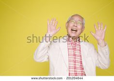 The old man surprised by raising both hands - stock photo