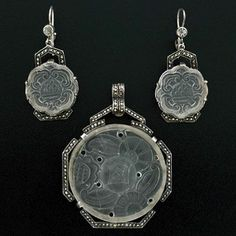 Deco S/S Lalique-Like Crystal & Marcasite Earring/Pendant Set. A fantastic carved crystal earring and pendant set from the Art Deco (ca1920) era! The gorgeous set has a lovely Lalique look and is comprised of a pair of earrings and a complimenting pendant. All three pieces depict a wonderful carved crystal design which is set in sterling silver and accented with marcasite stones. The pendant is particularly large in size and carries a complimentary design with a round crystal center.