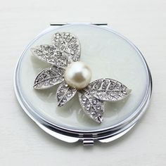 Crystal Flower Compact Mirror This crystal flower compact mirror is a perfect gift for lady. It is covered with white enamel glaze and mounted with bling-bling crystals. There are two mirrors inside. One regular mirror on top, the other 2x magnifying mirror on bottom. We can also make 3x magnifying mirror as per your request.