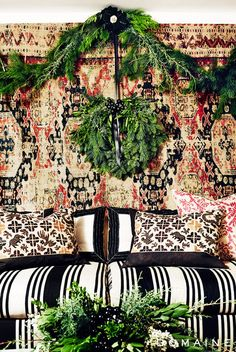 Jessica Biel's dreamy holiday room featuring black and white textiles and a traditional garland hung over a rich wall tapestry