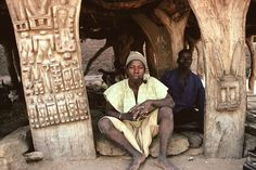 Africa | Man sitting at the entrance of a Taguna (a discussion hut, where the men meet up to discuss important matters). Traditionally carved wood pillars supporting a roof made out of millet. Dogon Country. Mali | ©Michel Renaudeau