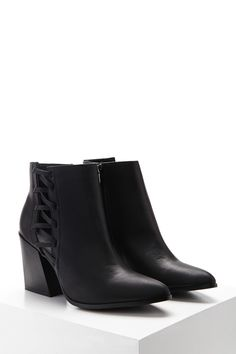 A pair of faux leather ankle boots featuring a crisscross cutout panel, pointed toe, a side zipper closure, and a block heel.