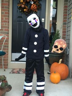 Five Nights At Freddy's Marionette Costume. I used the matte mask...you can't use sharpies on a glossy mask. My son didn't like the morph suit so I bought a black hood from the Halloween store. We sewed buttons from Walmart onto a black turtle neck & black costume pants.