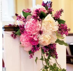 Church pew markers composed of pink and white peonies, lilacs, and ivy.