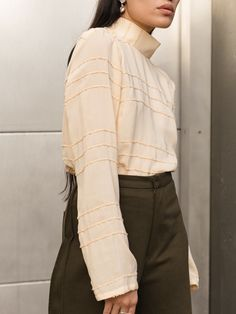 Delicate and feminie, the Silvae mock neck top is the perfect add on to your menswear-inspired trousers.