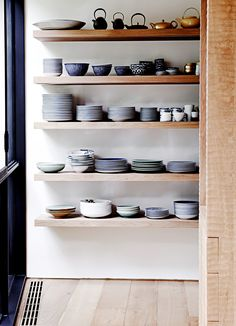 Clay plates and bowls on open shelves in kitchen