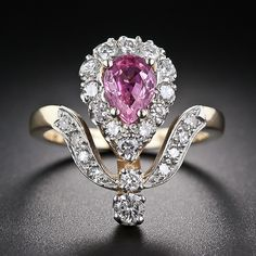 This ravishing, romantic and extra-feminine ring, highlighting an enchanting vibrant pink pear shape sapphire, was crafted during the mid-twentieth century in emulation of the timeless late-nineteenth to turn-of-the-century styles; the only real difference being the use of modern full-cut diamonds versus old cut stones.