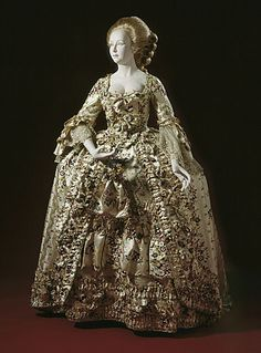 """1750-70 This gown & it's 3-dimensional ornamental surface incorporates 15+ yards of silk woven in a pattern of bouquets brocaded into a satin ground. Additional bands are gathered (ruched) along front openings & used as ruffles along petticoat hem. Edges of fabric used to enrich surface & finish w/a delicate looped thread trim & raveled ribbon trim, """"fly"""" fringe, which fluttered as wearer moved. Silk ribbon flowers & fabric bows on dress, petticoat, stomacher. Sleeves finished w/lace…"""