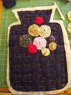 Quilted hot water bottle cover with yoyo embellishment. Very cute.