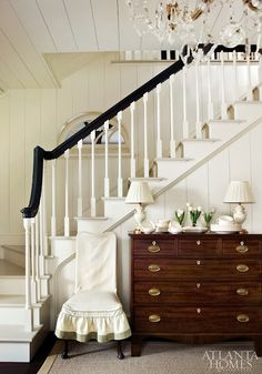 wood dresser + white walls + dark banister