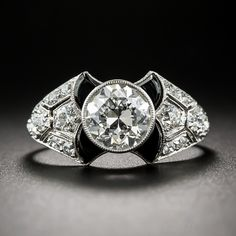 A unique and stunning, high-caliber engagement ring by America's premier purveyor of pretty things in small packages - Tiffany & Co. A collet-set 1.52 carat European-cut diamond beams like a bright-white headlight atop an artful and dramatic Art Deco mounting. The crystalline whiteness of the center stone is accentuated all the more inside four black onyx wing motifs set at the crests of the glittering, geometrically designed shoulders. Circa 1920s-30s.