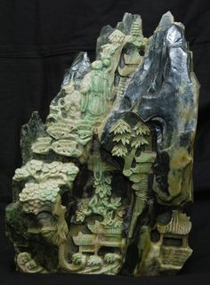 A large Chinese carved jade boulder group depicting Shou Xing with attendant on a mountain trail.