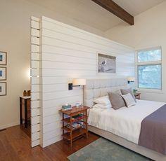 une tête de lit tapissée et une petite table de chevet en bois