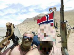 Members of Thorbrand, a unit consisting of Scandinavian fighters embedded with the Russian army in the desert regions of Palmyra and eastern Syria. They're affiliated with Skandinaviska Förbundet (Scandinavian League), a Far-Right group based primarily in Sweden. A group of them photographed on patrol in the desert, posing with a Norwegian flag. The flag's finial is a goat skull with the Black Sun or Sonnenrad, an occult Neo-Nazi symbol found originally in Himmler's Wewelsburg castle. Bush Jr, Colorado College, Norwegian Flag, Armed Conflict, Military News, Palmyra, Pop Culture References, Confederate Flag, Islamic World