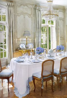 This is a beautiful, traditional french dining room, by adding a crisp white tablecloth (don't you just love the blue scallop edge!) blue and white china and flowers you instantly get a fresh and inviting table that your guests will want to linger at long after dinner!
