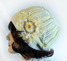 This womans or girls knit cloche hat is pale yellow and off-white. Multi-direction construction, including six square modules. The decorative ornament is sewn on. It is made of: tulle, a crocheted flower with beads and two buttons embellishing the center.  Pull down over the ears and forehead for extra warmth Knit tightly to add extra warmth and a firm feel. No seams and it is stretchy.  One-of-a-kind hat and so unique. Very attractive and will draw lots of comments and attention  Hand knit…