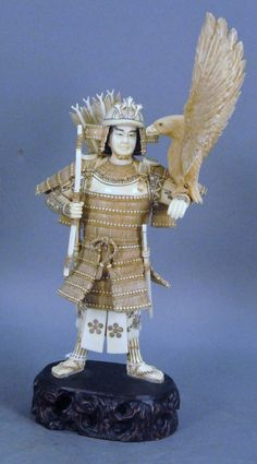 """Japanese carved ivory figure of a samurai with a eagle on his left arm, dressed in full suit with a bow and arrow, ht 10 1/2"""""""