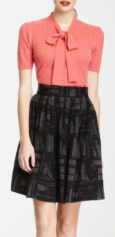 Orla Kiely pink short sleeve pussybow jumper with patterned black and grey skirt.