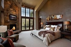 [162 white pine] Neutral bedroom with stone surrounding fireplace. Chocolate colored wall. Spacious and open.