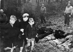 Image 45 of 45 A German mother shields the eyes of her son as they walk with other civilians past a row of exhumed bodies outside Suttrop, Germany. The bodies were those of 57 Russians killed by German SS troops and dumped in a mass grave before the arrival of troops from the U.S. Ninth Army. Soldiers of the 95th Infantry division were led by informers to the massive grave on May 3, 1945. Before burial, all German civilians in the vicinity were ordered to view the victims