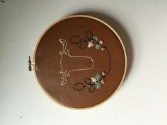 """Hand Embroidered Antlers with Wreath. Hand embroidered floral wreath on faux leather. One of kind, handmade by me, probably while relaxing on my porch swing. It is sure to be a standout addition to your home decor. ✒︎ M E A S U R E M E N T S ~ 7"""" hoop ✒︎ M A T E R I A L S ~ grey, yellow. green, white, pink, thread ~ faux leather ✒︎ S H I P P I N G ~ allow 3-8 days till shipment ✒︎ S H O P ~ See what else we have in stock here etsy.com/shop/WrightandCo ✒︎ F O L L O W We love social media!..."""