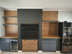Solid oak cladding against wall, solid oak box for fire wood. Storm grey MDF cupboards underneath with finger grip handles.  Kühn Houtwerke is situated in the Boland, Cape Winelands area. We specialize in kitchen cupboards, bedroom cupboards, solid woodworking, custom furniture and much more. For a quotation please send an email to khoutwerke@icon.co.za and we will be happy to assist. Follow us on Pinterest for our latest pins. Bedroom Cupboards, Kitchen Cupboards, Oak Cladding, Fire Wood, Wine Cellars, Bar Counter, Custom Furniture, Solid Oak, Quotation
