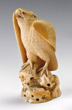 An ivory okimono of a hawk, Meiji period, perched on rockwork, with head facing forward and beak open, the plumage with incised details and the eyes inlaid, and with applied aogai details on the rockwork base, signed on a rectangular tablet Shungetsu 14.3 cm