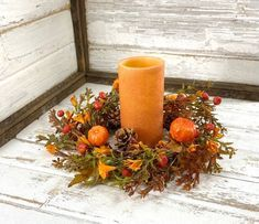 """Bring the fall season inside with this lovely large candle ring presented by Crooked Tree Creations. Filled with an abundance of rich autumn greenery, matching oak leaves, pine cones, wispy orange fillers and assorted pumpkins, this versatile piece is perfect for display as a small wreath, candle ring or as the base of a beautiful seasonal centerpiece.This floral measures 6.5"""" inside diameter and 15""""-16"""" outer diameter depending on wreath adjustment. All dimensions are approximate. ***This listi Lemon Centerpieces, Pumpkin Centerpieces, Pumpkin Candles, Fall Candles, Small Wreath, Crooked Tree, Yellow Candles, Candle Rings, Large Candles"""