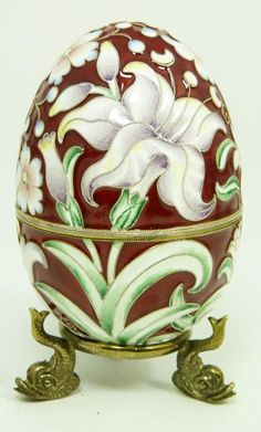 Russian silver egg with beautiful enamel floral design over rust ground. Gold wash interior. Includes silver footed stand with figural fish design.