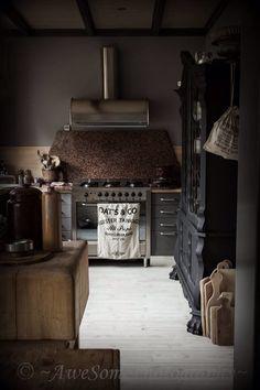 industrial extraction hood, dark stone splash back, hits of light wood and antique unit softens, light floor!
