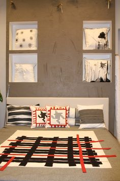 Copriletto in cotone grigio con applicazioni. Cuscini sullo sfondo, nelle nicchie, in cotone dipinti a mano. Cuscini stampa pied de poule.