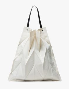 Modern, textured tote from Iittala in collaboration Issey Miyake in Ivory. Innovative pleating techniques add texture dimension. Black cowhide top handle attached with visible silver hardware. Roomy interior. Unlined.    • Original Issey Miyake fabric she