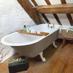 C0unTRY  ATTic Bathr00m  The elegant roll-top clawfoot creates a focal point in this bathroom. The original beams and wooden floor add a rustic, country element.