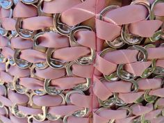 Close up of material made from weaving ribbon in soda can tabs, also by cardboard prom dress girl.