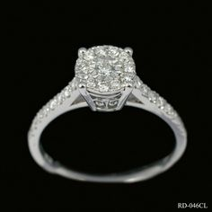 Delightful diamond cluster ring in 9ct white gold. This pretty design comprises of a single round cut centre stone surrounded by an 11 x round cut diamond border. The ornate mount adds to the appeal of this charming piece of jewellery. £450