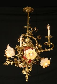 """Late 19th century Louis XV-style French Rococo dore' bronze electrified gasolier chandelier with """"sang de boeuf"""" porcelain vase shaped central support entwined with branches extending to foliate shaped arms holding 7 lights with art glass rosette shaped shades, 40""""h x 30""""w."""
