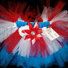 The 4th of July tutu is bursting with patriotic colors. This sparkling tutu has lots of extra 'puff' with its double layers of tulle. It is fashioned with a bottom layer of bright blue tulle and the top layer with red, white and glitter white tulle. Two mini white peonies and a triple layered jeweled lily are the finishing touch. Perfect for a day filled with family, BBQ's in the park, sparklers and fireworks. Your little firecracker will receive lots of 'oh's' and 'ah's!'