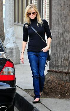 Reese Witherspoon in a black sweater, jeans, crossbody bag, and flats