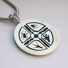 Zhooniyaa Mashkiki Waawiyeyaatig (Silver Medicine Wheel). Medicine wheel featuring personalized/customized symbols of four quadrants and a turquoise cabochon in the middle. The eagle feather cross in the middle symbolizes the quadrinity of all life that lies at the base of Creation, or the Cosmos. The circle of the wheel is WAAWIYEKAAMIG, the Universe itself.  #ojibwe  #ojibweart  #ojibwejewelry  #ojibway  #anishinaabe  #anishinaabejewelry  #nativeamericanjewelry  #zhaawanogiizhik  #zhaawano