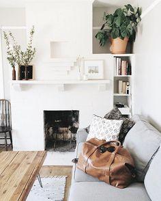Living room with fireplace, primitive furniture, indoor plants.