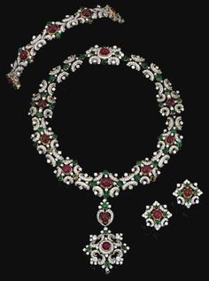RUBY, EMERALD AND DIAMOND PARURE.  Comprising: a pendant necklace designed as a series of graduated cabochon rubies in pinched collets set with scroll borders of cabochon emeralds and brilliant-cut diamonds, the pendant detachable and wearable as a brooch, length approximately 395mm, together with a bracelet, length approximately 160mm, and a pair of ear clips en suite, all mounted in white and yellow gold and signed Vitzthum