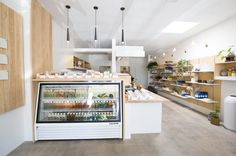 Concrete floors, wooden counters, industrial ceiling lights and glass refrigerator Cafe Bar, Cafe Restaurant, Restaurant Design, Juice Bar Interior, Juice Joint, Juice Bar Design, Juice Store, Smoothie Shop, Moon Juice