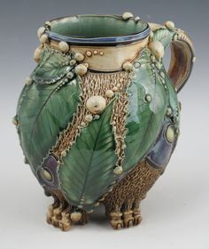 Carol Long Title: caterpillar mug   Description: wheel thrown with cone 5 b-mix, pulled handles,  hand built feet, slip trailing, commercial cone 5 food safe glazes, fired to cone 5 oxidation  Dimensions: 5.50 H X 5.50 W X 4.50 D Inches   Price: 295.00